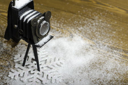camera: Christmas snowflake and camera on a wooden background. Stock Photo