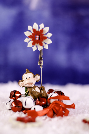 resfriado: Monkey holding a Christmas wreath in the hands of a snowflake. On a snowy background.