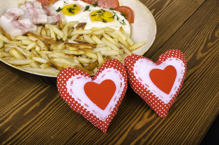 bacon love: Breakfast for two on Valentines Day. Frying pan with a meal and two hearts. On wooden background. Stock Photo