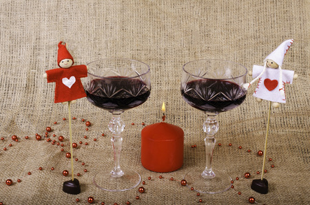 rest day: Glasses of wine, candle, chocolates and toys on the background of burlap. Stock Photo