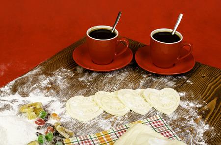 frutos secos: Corazones de pasta, dos taza de café roja y frutos secos en el fondo de madera.
