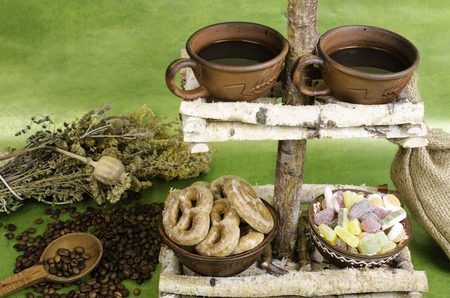 country style: Two cups of coffee, coffee beans, cookies and fruit candy on a stand made of wood. In country style. Stock Photo