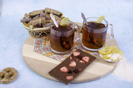 tea and biscuits: Tea, biscuits and chocolate on a wooden tray. Close-up. Stock Photo