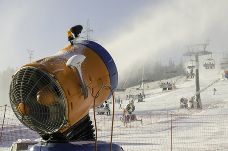 skiers: Snow machine throws snow in  mountains. Skiers on the lift.