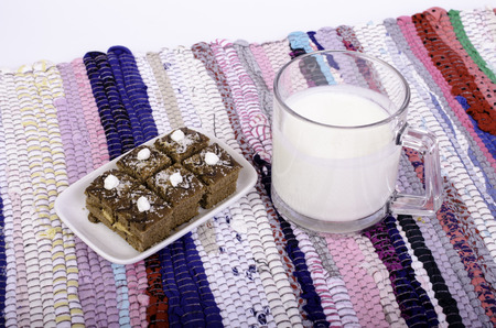 matting: Cup of milk and biscuit on multi-colored matting. Stock Photo