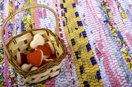 matting: Basket with sweets in form of heart on multi-colored matting. Stock Photo