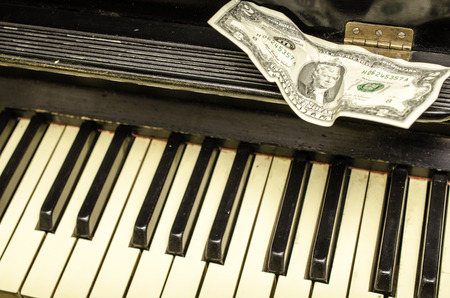 old piano: Keys of the old piano and banknote two dollars. Close-up. Stock Photo