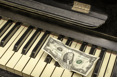 old piano: Keys of  old piano and banknote two dollars. Close-up.