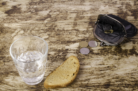 poorness: A glass with liquid, rusk and purse with coins.