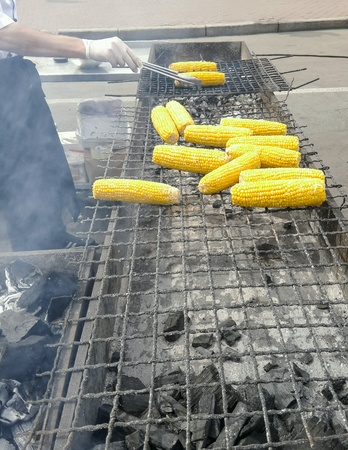 coocing: chef cooks corn outdoor.