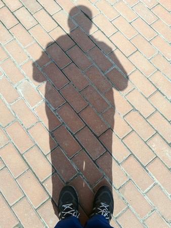 man: Shadow of the man on the sidewalk.
