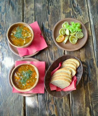 ollas de barro: Sopa en macetas de barro sobre un fondo de madera. Foto de archivo