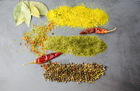 surface closeup: Various spices on a black surface. Close-up.