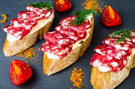 Sandwiches with salami, tomato and dill on a dark background.