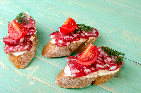 Sandwiches with salami, tomato and dill on a blue background.