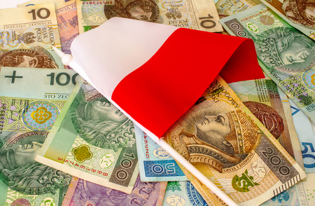 polish flag: Polish zloty. Many banknotes, coins of different denomination and the Polish flag.
