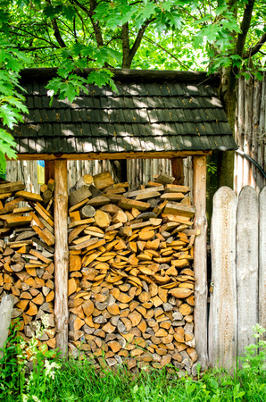 under fire: Fire wood under a canopy outdoor near the fence. Foto de archivo