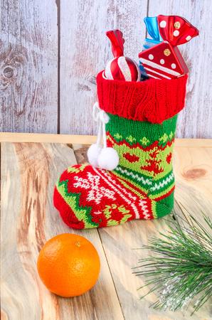 botas de navidad: Sobre la mesa hay una botas de Navidad con regalos. Muy cerca se encuentran mandarina y ramas de abeto.