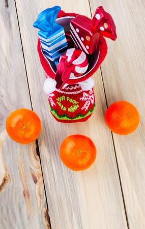 botas de navidad: Sobre la mesa hay una botas de Navidad con regalos. Muy cerca se encuentran mandarina.