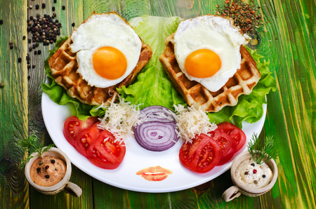 Fried eggs and tomatoes on a white plate. With spices and herbs.
