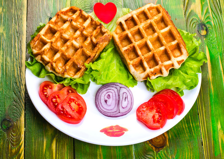 Liege waffles, tomato, onion and lettuce on a white plate. On wooden green background.