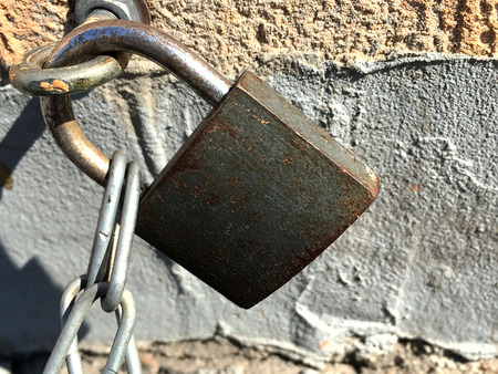 fastens: The old lock fastens the chain to the ring in the wall. Close-up.