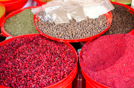 Spices on the market in colorful containers. Horizontal arrangement.