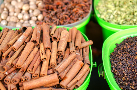 Cinnamon and other spices on the market in colorful containers. Horizontal arrangement. Stock Photo