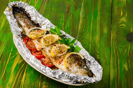 aluminum: Fried fish in foil on a wooden background. With tomatoes, lemons and spices.
