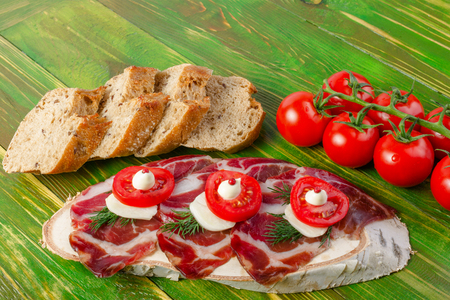 uncooked bacon: Slices of ham Serrano, dill branches and tomatoes on birch stump, slices bread. On a wooden green background.