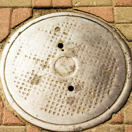 Manhole on the sidewalk in a city road. Urban background. Square. Close-up. Stock Photo