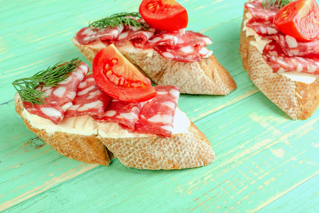 Fresh tasty salami sandwiches. Appetizing sandwiches with smoked sausage, cream cheese and tomatoes. On blue wooden background. Close-up.