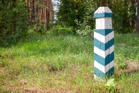 Territorial sign. Wooden green and white  striped post in the forest. Forest area designation. Outdoors. Close-up.