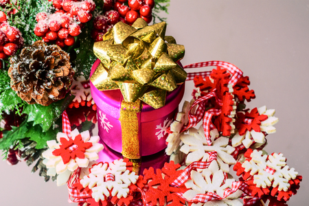 Christmas decorations. Decorative gift decorated with ribbon with colorful snowflakes made of cloth. And also red berries. On the reflective surface. Selective focus. Space for text. Close-up.
