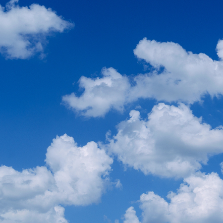 White fluffy clouds in the vast blue sky. Abstract nature background.