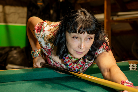 Beautiful adult woman concentrates aiming billiard cue on the green billiard table. The concept of active leisure. Close-up. Banco de Imagens - 109926675