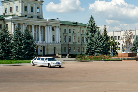 Luxury white wedding limousine in Khmelnitsky on central square near the town council. Outdoors.