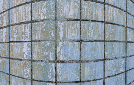 Wall is covered with old rough shabby blue tiles. Can be used as background. Close-up.