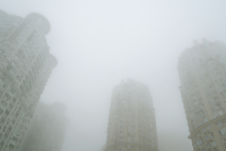 Foggy сityscape scene. Fog on the city street. Modern high-rise residential buildings or office buildings are tightly covered with thick white fog. Close-up.