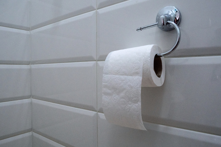 Roll of white toilet paper is hanging in the restroom on the wall. Close-up. Stock Photo
