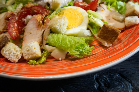 Caesar salad in red plate. Caesar salad consists of roasted chicken breast, iceberg lettuce, tomato. Popular dish of European cuisine and cuisines of other countries of world. Close-up. Stock Photo
