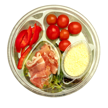Healthy fast food in a transparent container. Vegetable salad for quick cooking with tomatoes, bell peppers, jamon and lettuce. On gray background. Top view. Isolated. Close-up. Stock Photo
