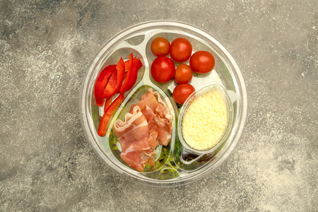Healthy fast food in a transparent container. Vegetable salad for quick cooking with tomatoes, bell peppers, jamon and lettuce. On gray background. Top view. Close-up.