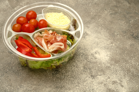 Healthy fast food in a transparent container. Vegetable salad for quick cooking with tomatoes, bell peppers, jamon and lettuce. On gray background. Close-up. Reklamní fotografie