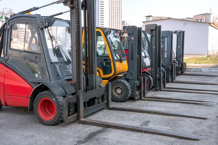 Several cargo loaders are lined up in an open construction site. Outdoors. Editorial