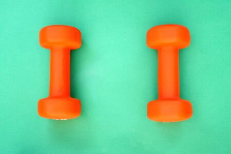 Doing sports. Two orange dumbbells lie on a green surface.