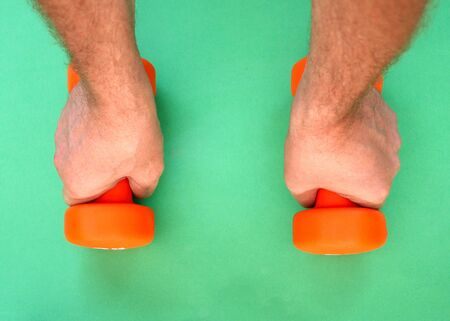 Two orange dumbbells lie on a green surface. Man hands take barbells. Stock Photo