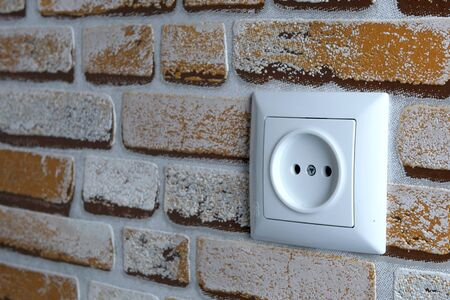 Electrical outlet in the brick wall of the house. Interior of the room. In room. Selective focus. Close-up.