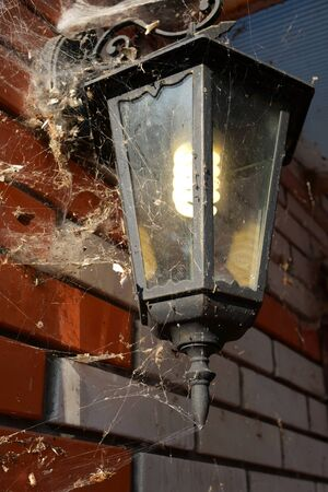 Old electric lantern, overgrown with spiderwebs, on brick wall of abandoned  house. Close-up. Stock Photo