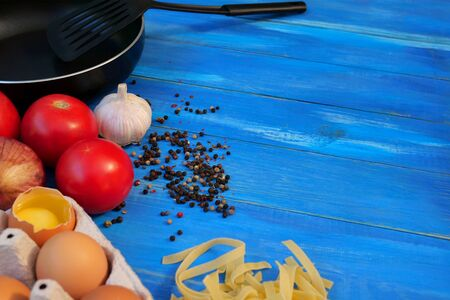 Breakfast Set. Frying pan, tomatoes, raw eggs, onions, garlic, spices, dry pasta. Selective focus. Copy space. On blue wooden background. Close-up. Stock Photo